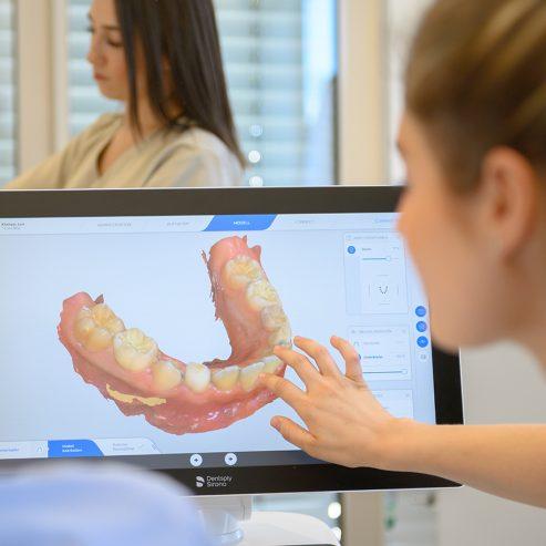 Eine Hand zeigt auf einen Monitor mit 3D Modell vom Gebiss eines Patienten