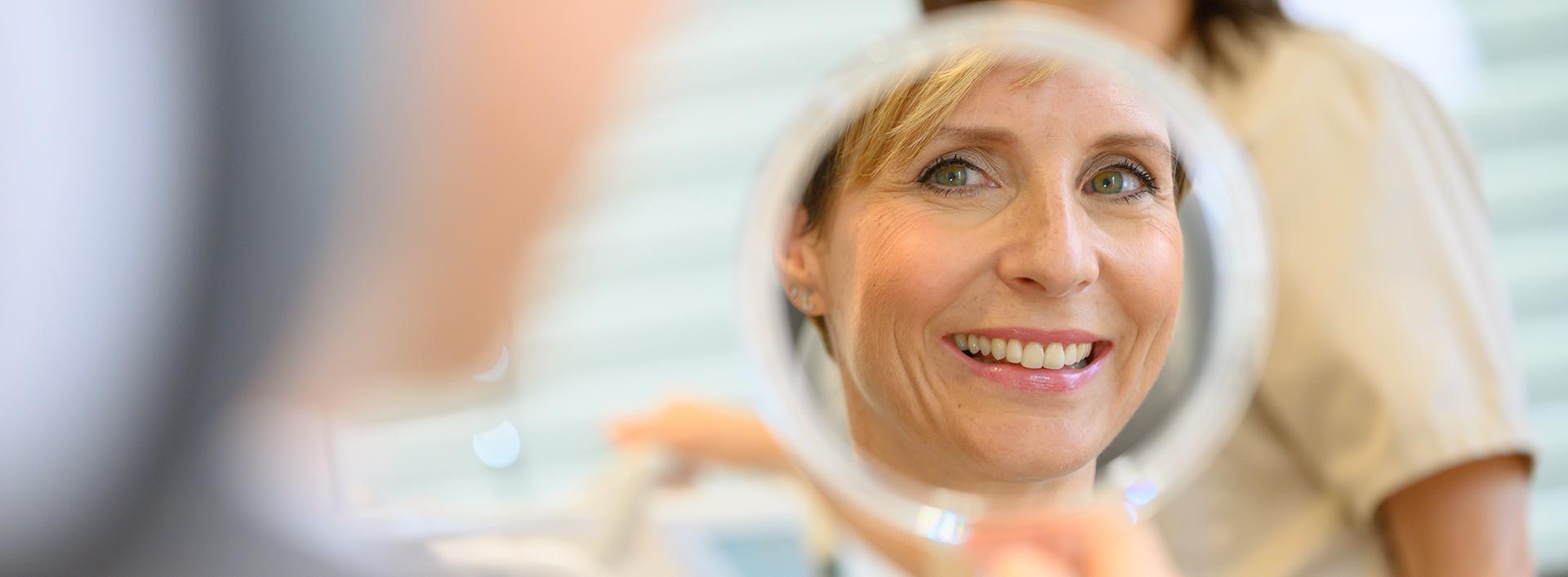 Lächelnde Frau sieht ihre Zähne im Handspiegel an