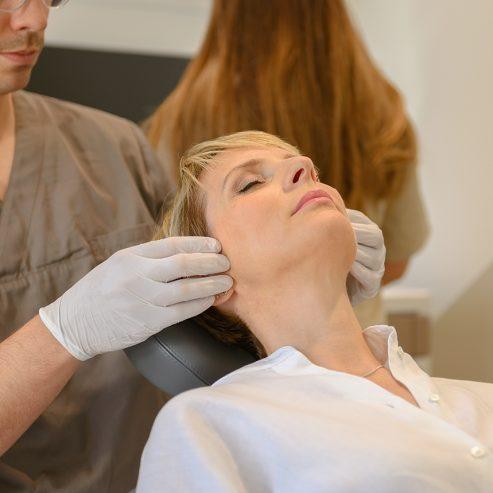 Arzt tastet vorsichtig den Kiefer einer Patientin ab