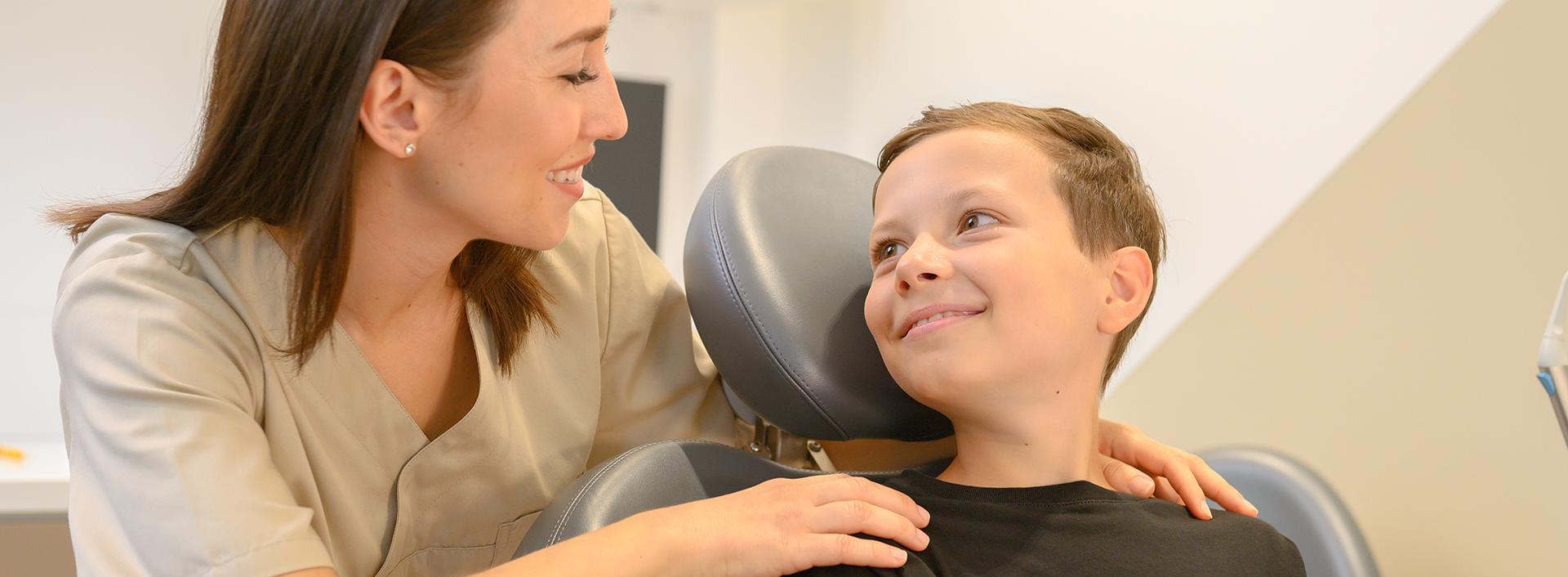 Zahnarzthelferin erklärt einem jungen Patienten etwas