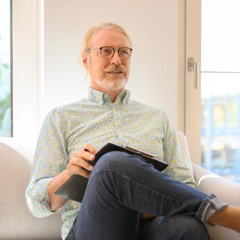 Patient sitzt im Wartezimmer mit einem Bogen zum ausfüllen - quadratisches Format