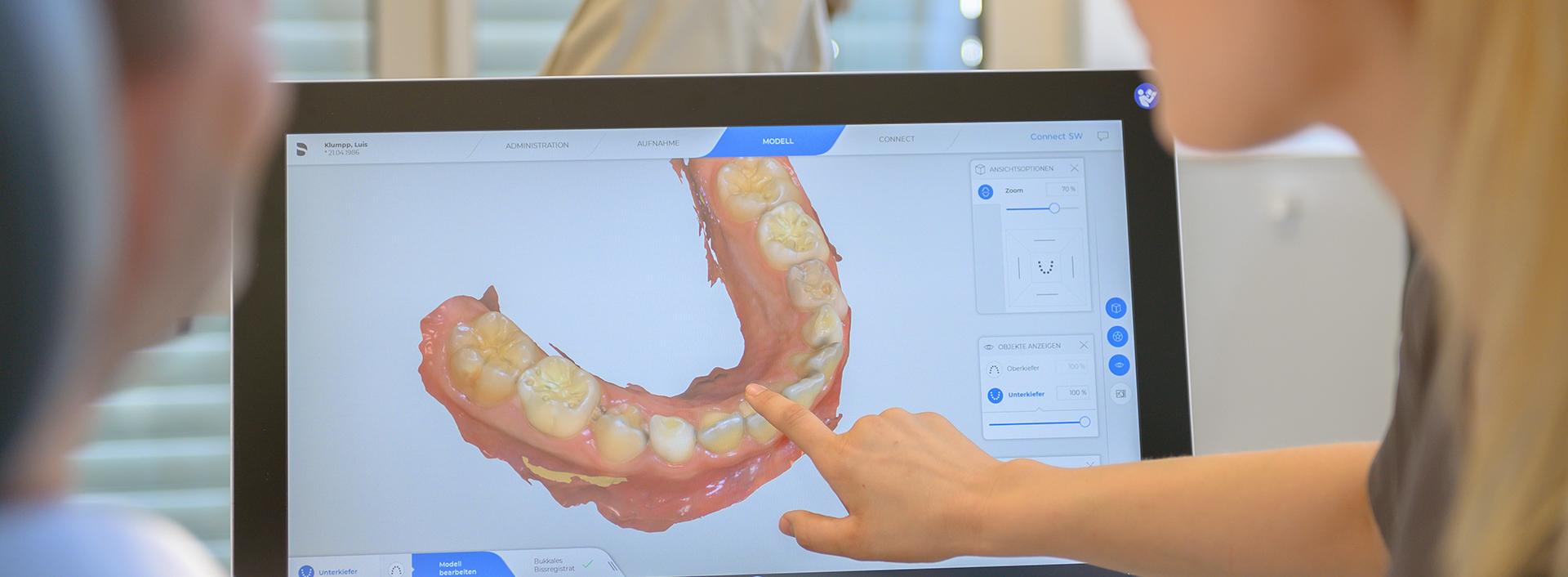 Ärztin zeigt auf einen Monitor mit 3D Modell vom Gebiss eines Patienten
