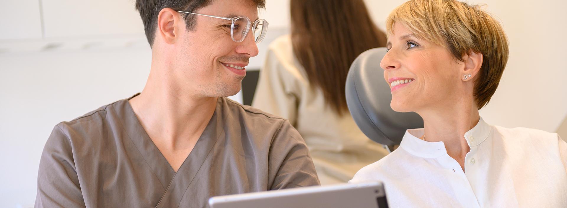 Arzt zeigt der Patientin etwas auf einem Tablet