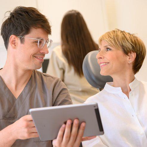 Arzt zeigt der Patientin etwas auf einem Tablet - quadratisches Format
