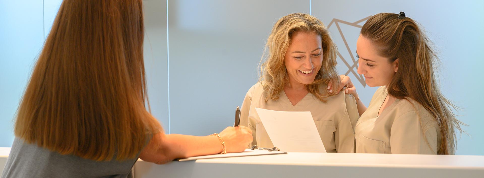 Zwei Arzthelferinnen unterhalten sich mit einer Patientin am Empfang