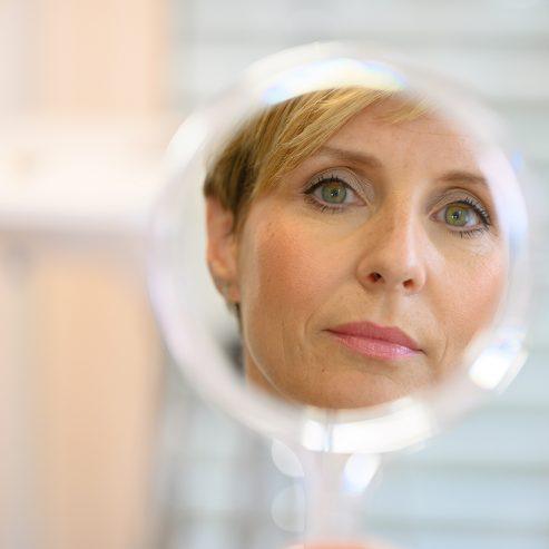 Frau die sich in einem Handspiegel betrachtet - quadratisches Format