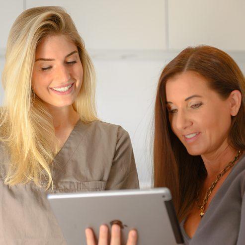 Ärztin erklärt der Patientin etwas auf dem Tablet - quadratisches Format